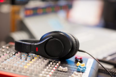 Closeup of headphones on Sound Mixer In Professional Radio Studio